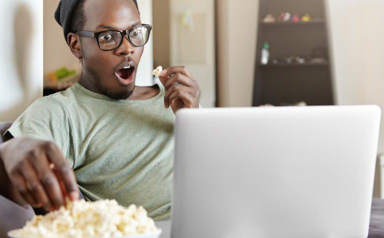 homem assistindo a filme no computador com cara surpresa e pegando uma pipoca