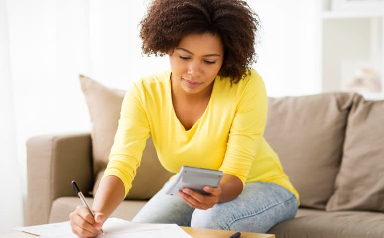 Mulher escrevendo com calculadora na outra mão