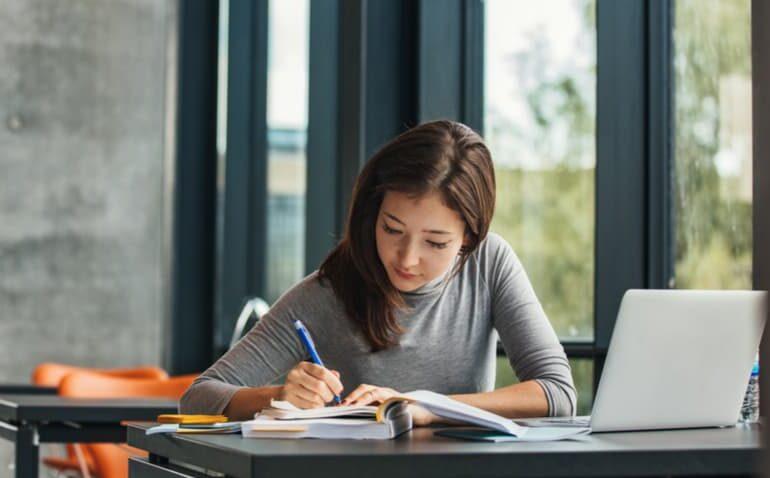 Mulher estudando com computador e livros