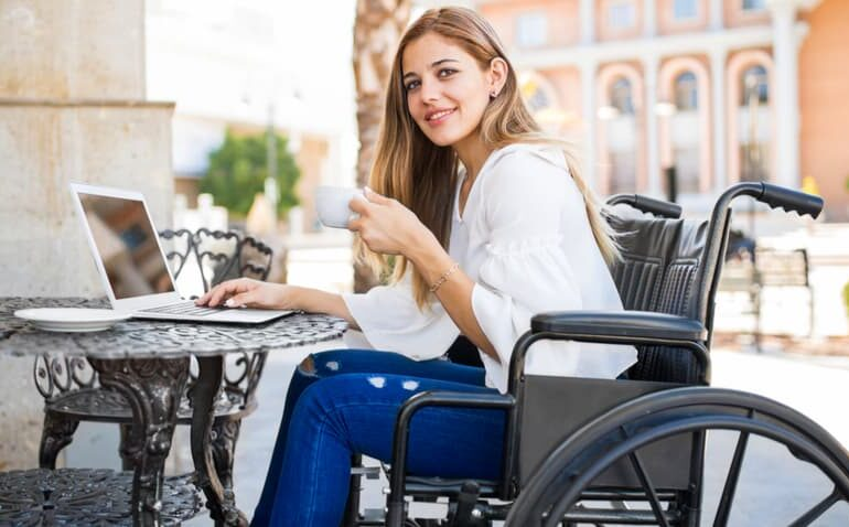 Mulher de cadeira de rodas tomando café e usando computador